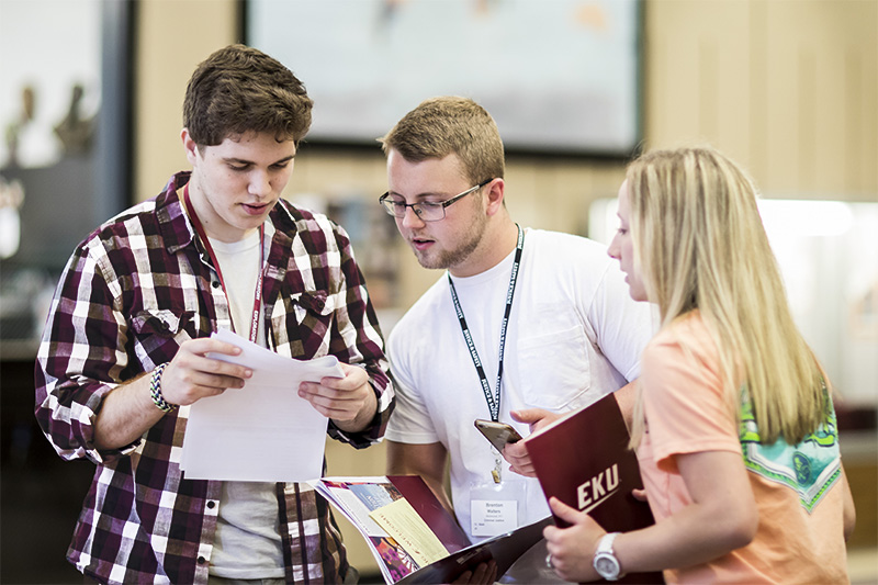 Three EKU students checking a schedule.